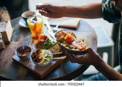 Young man enjoys big and tasty breakfast at downtown cafe, prepares delicious sandwich or toast with avocado spread and smoked salmon on top. chia seeds with yoghurt for dessert