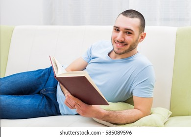 Young man enjoys reading book at his home.Man reading book