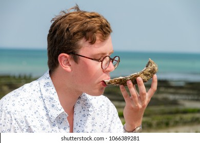 Young man enjoys the taste of a rare big oyster called a pied de cheval (horse's hoof) at the french coast of Brittany (Bretagne) in Cancale, France on a summer day