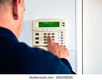 Young man entering authorization code pin on home alarm keypad. Home security concept