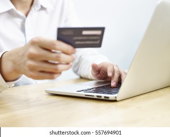 young man entering credit card information while shopping online using laptop computer
