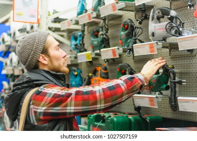 Young man enthusiastically compares electric jig saws at a large store