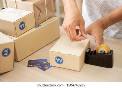Young man entrepreneurs are wrapping products  to send products by mail to customers who order products online.Online Shopping and e-Commerce ,SME concept.