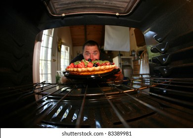 a young man is excited about the fruit tart he just baked in his oven