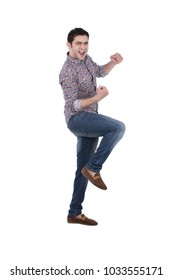 A young man excited raising his hands and one leg as he yelling excitedly, isolated on a white background.