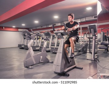 young man exercise bike, cycling, stationary exercising. Indoors gym.