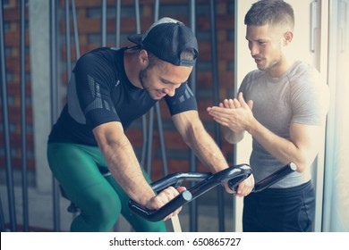 Young man exercise on stationary bikes in fitness class. Man workout in gym. Exercise on elliptical machine. Man personal trainer.