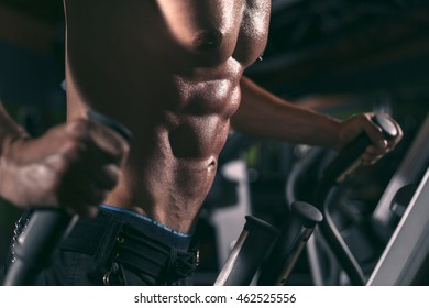 Young man exercising in the gym on the elipsoid stepper