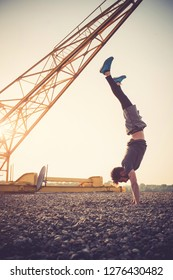Young man exercising hand-stand outdoors by the crane