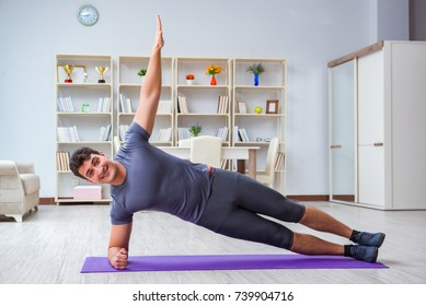 Young man exercising at home in sports and healthy lifestyle concept