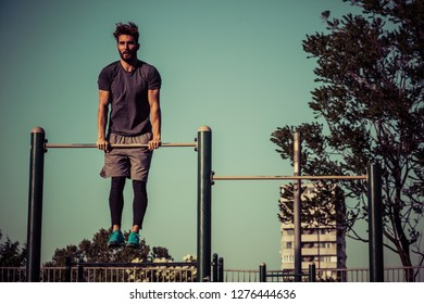 Young man exercising on gymnastic bar at public gym in the morning