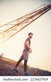 Young man exercising outdoors by the crane