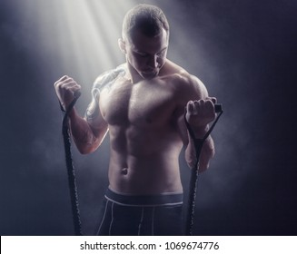 Young man exercising with rubber band against a dark background. Sports concept