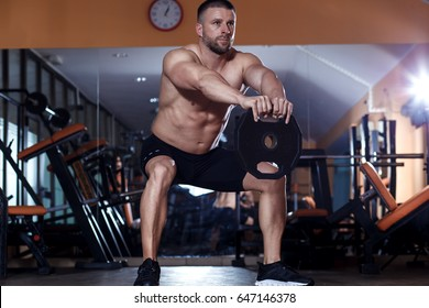 Young man exercising with weight in the gym.