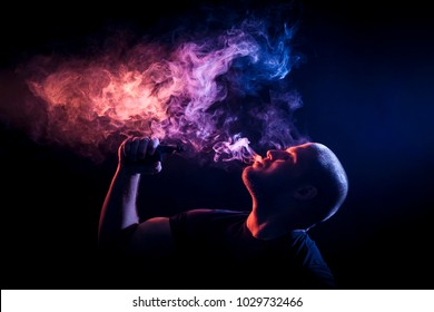A young man exhales a cloud of colored smoke of purple and orange color on a black isolated color all the back is covered with  smoke. Harm to smoking on the example of a young mugger