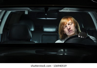 A young man exhausted and falling asleep while driving his car at night