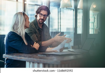 Young man explaining his idea of business to mature female colleague at work. Business people having a meeting for project discussion.