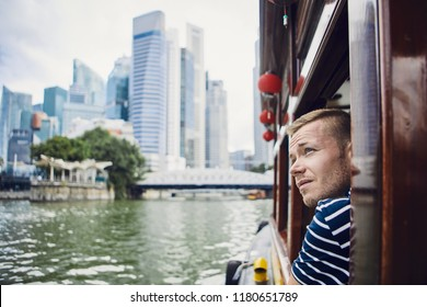 Young man exploring city and looking out from river boat in Singapore.