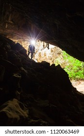 Young man exploring mystery cave with a torch, Phraya Nakhon Cave is a large cave which has a hole in the ceiling allowing sunlight to penetrate, most popular attraction at Prachuap Khiri Khan. Thai.