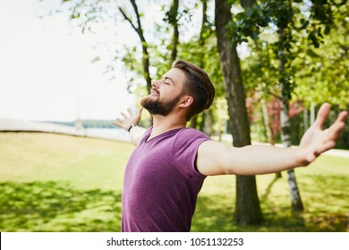 Young man extending arms and enjoying the sun outdoors in the park