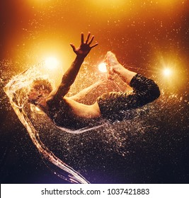 Young man extreme dancer flying through splashes of water. Vibrant background with warm lights.