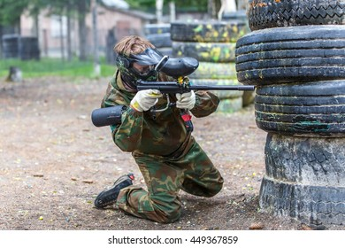 Young man in extreme process of paintball game