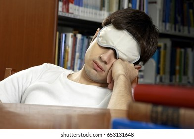 Young man with eye mask sleeping in the library