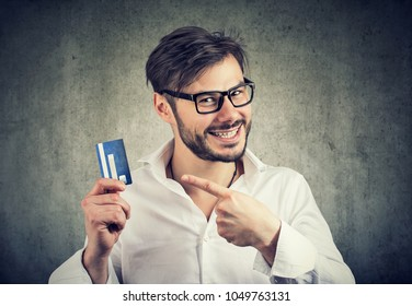 Young man in eyeglasses pointing at credit card in hands satisfied with choice of best bank