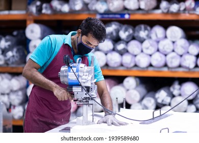 Young man in a face mask and protective chain gloves at work. Man with cutter machine and personal protective equipment at garment industrial work place. Fabric cutter in Asian textile garment factory - Shutterstock ID 1939589680