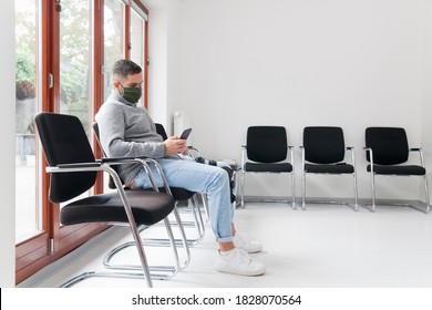 Young man with face mask sitting in a waiting room of a hospital or office looking at smartphone - focus on the man