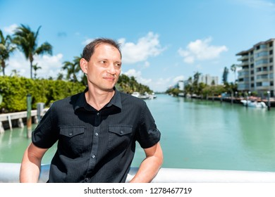 Young man face wearing black shirt standing leaning on bridge railing in Bal Harbour, Miami Florida with green ocean Biscayne Bay