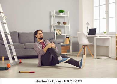 Young man fallen from ladder sitting on floor and suffering from awful pain. Unlucky guy fell off ladder while doing home repairs and hurt his knee. Concept of dangerous domestic accidents - Shutterstock ID 1897152193