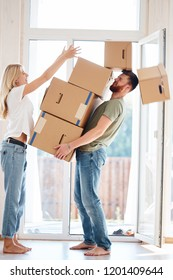 Young man Falling Stack Of Cardboard Boxes Over back In House while woman place boxes on stack