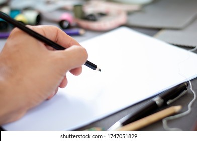 Young man fashion designer drawing on white paper for fashion design collection. Designer drawing fashion clothing at workshop. Empty white paper for drawing by fashion designer.