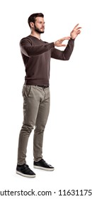 A young man in fashionable casual closes stands on a white background with hands as if pressing invisible buttons. Information control. High-tech solutions. Generation of new ideas.