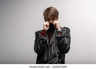 A young man with a fashionable hairstyle in red golf in a leather jacket in black jeans covers his face with his hands and looks into the camera in the studio near a white wall. Attractive cute guy.