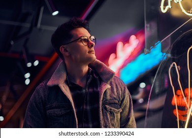A young man fashionably dressed standing in the street at night. Illuminated signboards, neon, lights.
