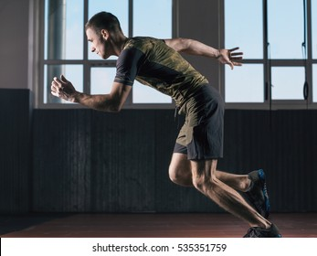Young man fast running. Sports training in the gym.