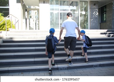 young man, father leads two children with school bags, hold hands, climb the stairs, Back to school concept