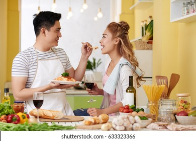 Young man feeding his girlfriend with spaghetti he made