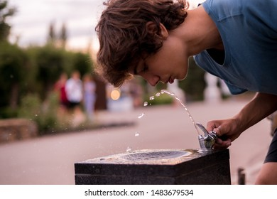young man feel thirsty,  drinking water from public city fountain