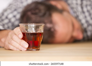 Young man feeling alone and drinking too much alcohol in his own home at the table