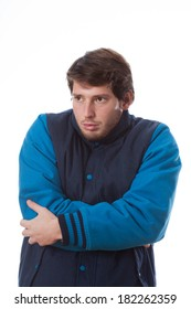 Young man feeling cold and wearing jacket