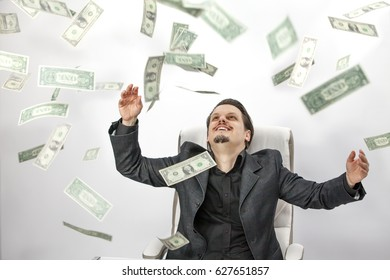 A young man is feeling happy because he is rich. He is throwing the money in the air.