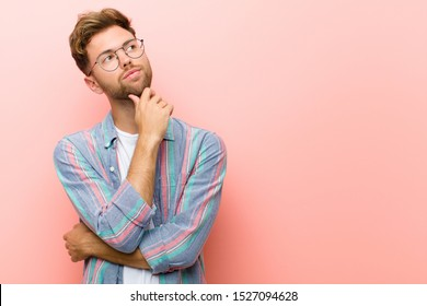 young man feeling thoughtful, wondering or imagining ideas, daydreaming and looking up to copy space against pink background