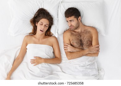 Young man feels bored as lies in bed, looks at wife who has pleasant dreams, wants to speak or flirt, has unhappy or upset expression. Attractive man can`t sleep well after quarrel with girlfriend