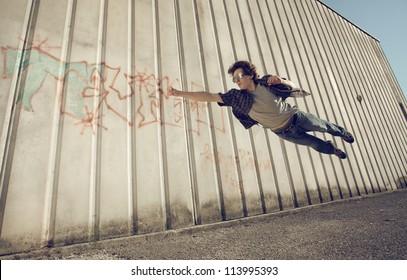 Young man feels like a superhero, flying free.