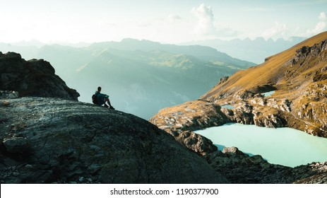 Young man feels relaxed at sunset in Swiss Alps at the glacial teal lake on the Pizol 5-lakes hike