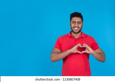 Young man felling love doing heart sign with fingers on his chest, on a blue background.
