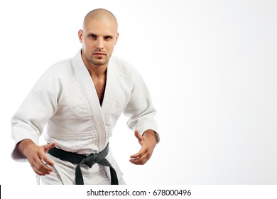 Young man fighter in white kimono with black belt for judo, jujitsu posing in combat pose on isolated white background